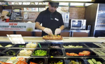 Roberto Castelan makes a sandwich at a Subway sandwich franchise in Seattle