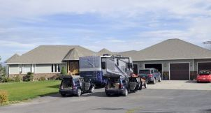 sport utility vehicles, a sports car and a motor home sit in the driveway of Doris Nelson's home
