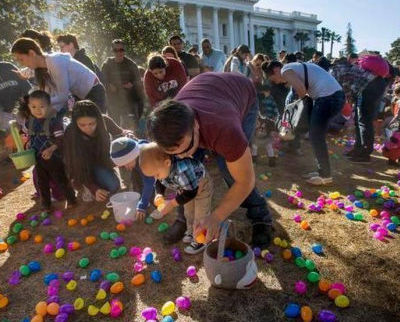 Rich Smith of Sacramento, center, helps his son Charlie gather plastic Easter eggs