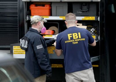 Federal Bureau of Investigations evidence response team members at their evidence truck looking over paper in the parking lot where Allure Medical has an office in Shelby Township