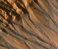 a gully on Mars, thought to form by flowing water, trends downslope along a crater wall