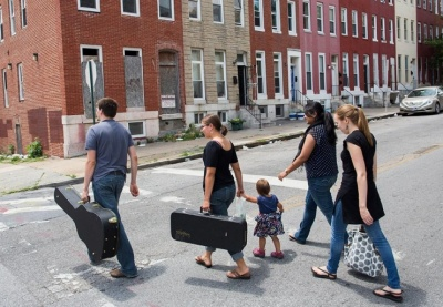 Matthew Loftus, left, walks home with his wife, Maggie, and daughter, Naomi, after attending Sunday service at New Song Community Church in the impoverished Sandtown neighborhood in Baltimore