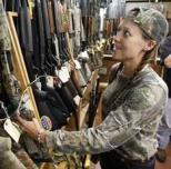 Rachel Smith, 32, of Richmond, looks over shotguns at the Bob Moates Sport Shop in Richmond, Va.