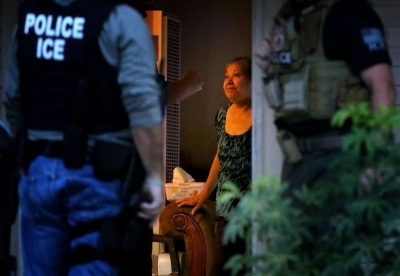ICE Enforcement and Removal Operations officers, in search of 32-year-old Hugo Medina, question his mother Magdalena Medina, 69, about his whereabout