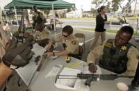 Los Angeles County Sheriff Deputy Jeff Gordon, right, and colleagues examine and process weapons