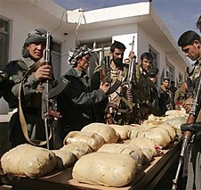 Afghan border policemen view confiscated opium