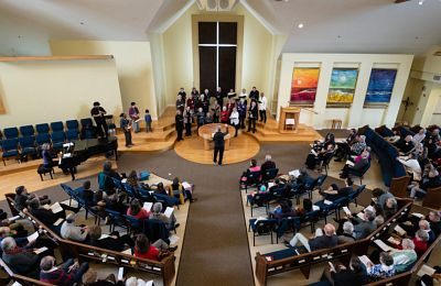 Members of First Congregational Church of Bellingham celebrate the grand opening of the Ground Floor with prayers and song during a worship service