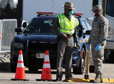 A New York State Trooper works with a member of the military at the third checkpoint to a new coronavirus drive-thru testing site that is up and running at at Jones Beach State Park, New York