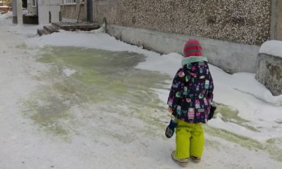 A girl stands near green snow in Pervouralsk, Russia