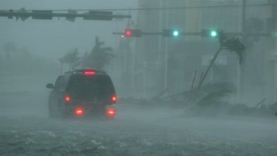 An SUV passes through flooding in downtown Naples, Florida, as Hurricane Wilma passes