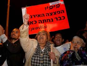 "Israelis hold up a sign in Hebrew that reads, ""Bibi! the Iranian bomb already landed here (the taliban)"" as they protest"