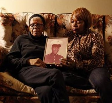 Alma Murdough and her daughter Cheryl Warner hold a photo of Murdough's son