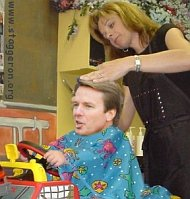 John Edwards gets a haircut in two Americas
