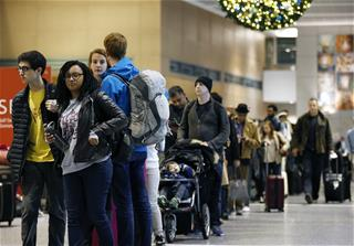 Passengers wait in line at a security checkpoint at Logan International Airport