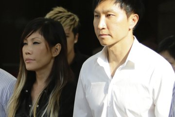 City Harvest Church founder Kong Hee (R) holds the hand of his wife Sun Ho, also known as Ho Yeow Sun