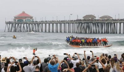 Sixty-six surfers exalt as they set a Guinness World Record Saturday for most riders on a board.